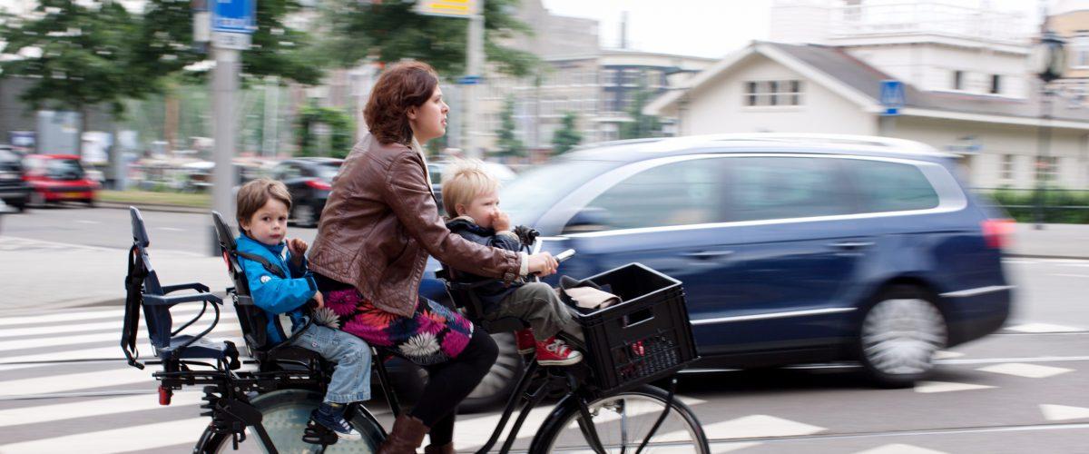 Een vrouw fietst met twee kinderen op de fiets door Rotterdam